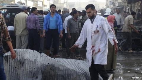 A man wearing a white coat stained in blood, inspects a site hit by what activists said were barrel bombs dropped by forces loyal to Syria's President Bashar al-Assad in the northern town of Atareb, in Aleppo province, 24 April  2014 Activists said dozens were wounded after planes dropped barrel bombs on the town